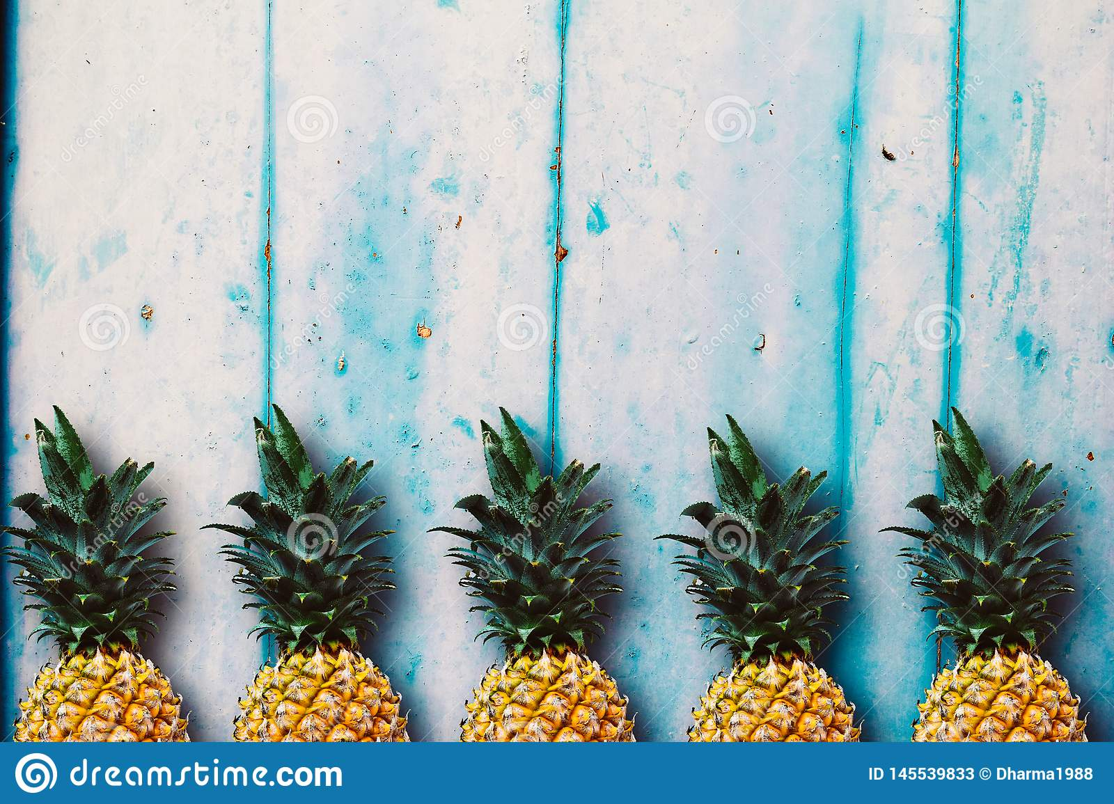 Ripe pineapples over the blue wooden table.