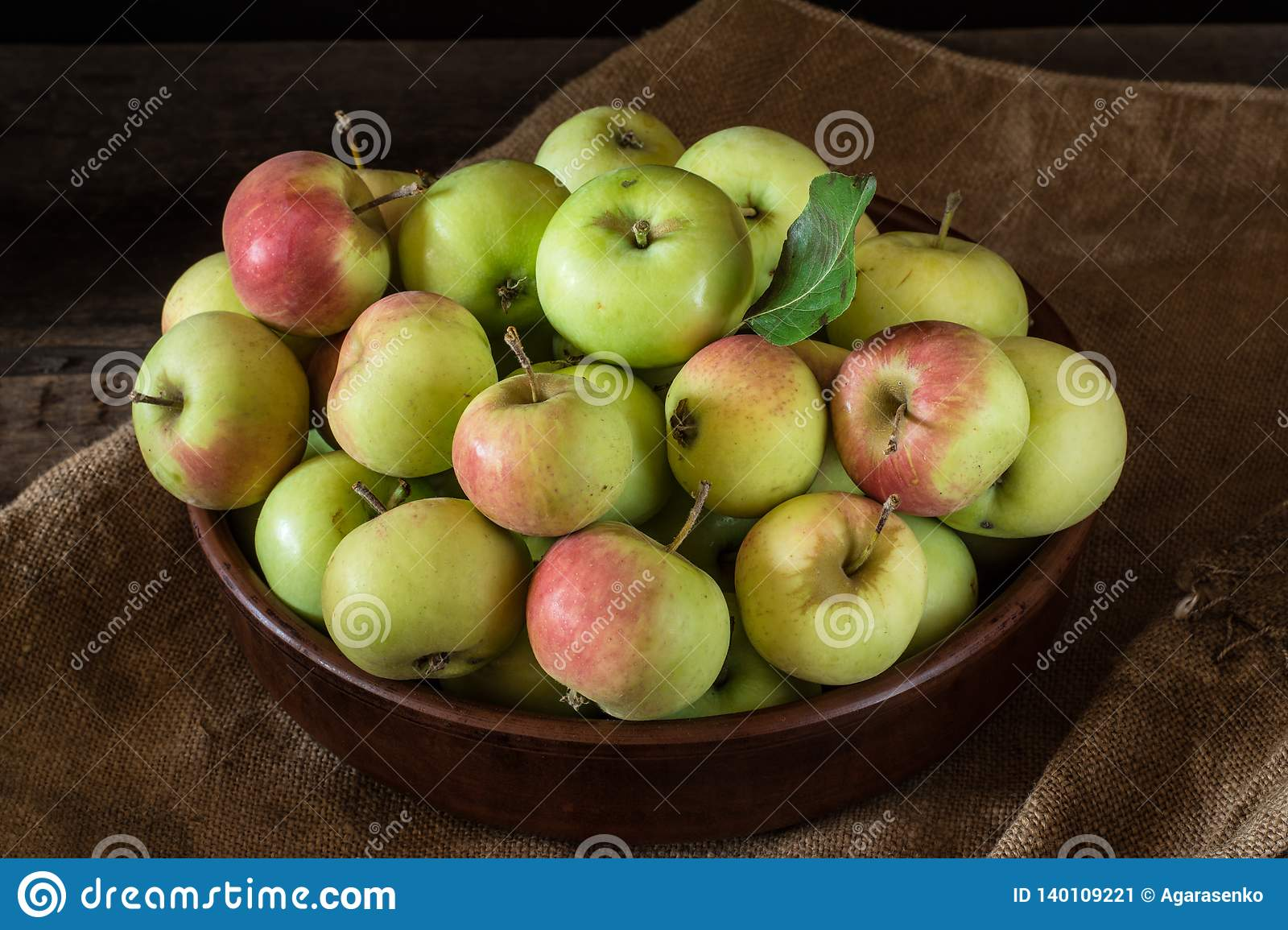 Ripe red and green apples on wooden background. Apples in bowl. Garden fruits. Autumn fruits. Autumn harvest.