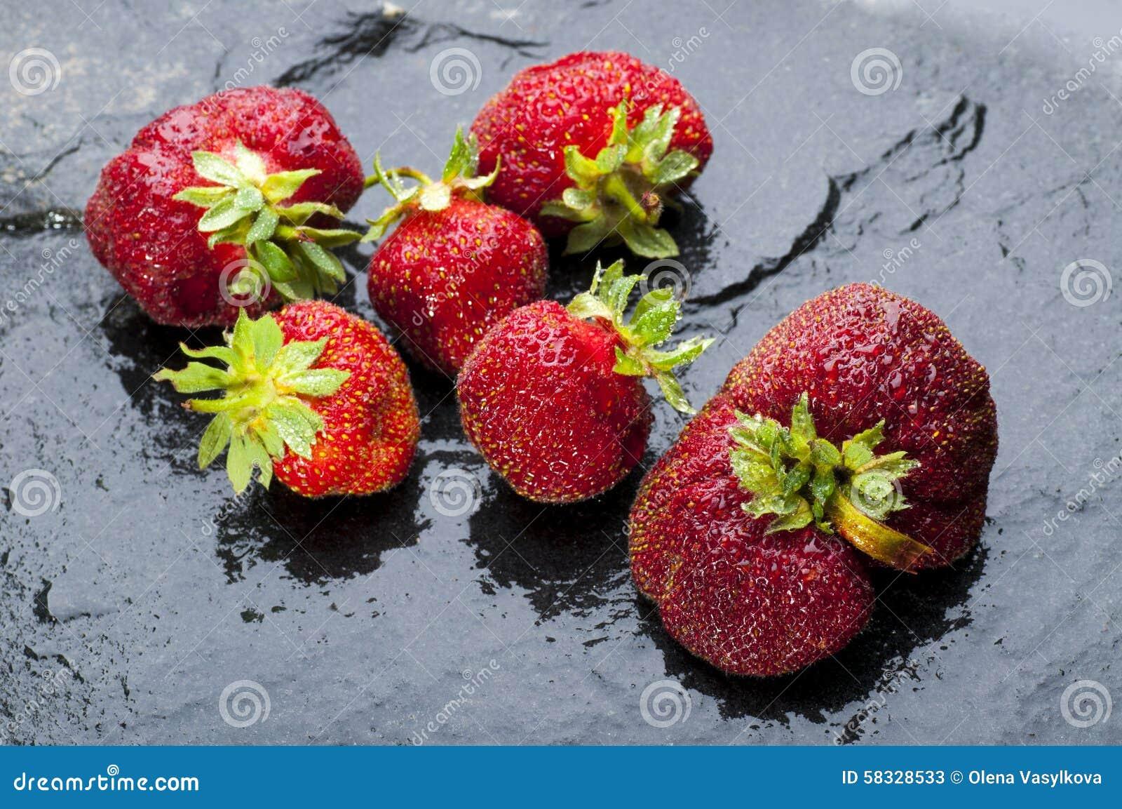 Ripe strawberries on black stone background