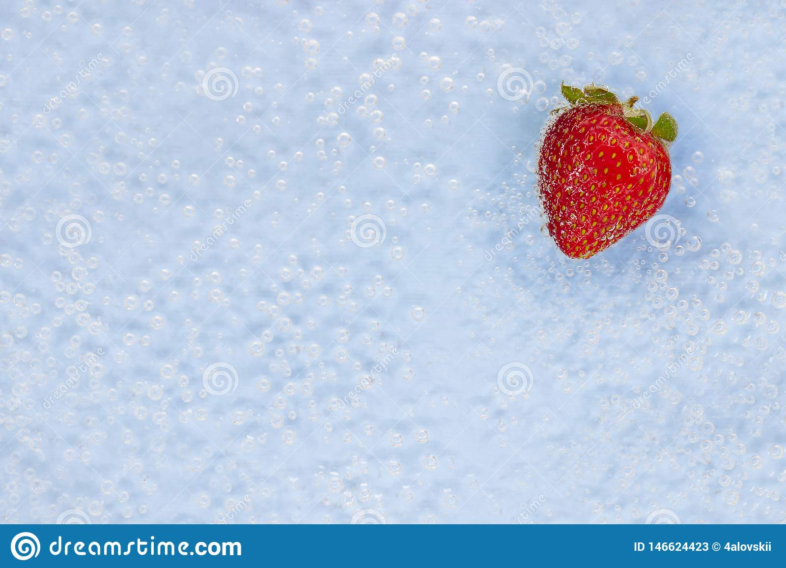 Ripe strawberry in blue water with air bubbles