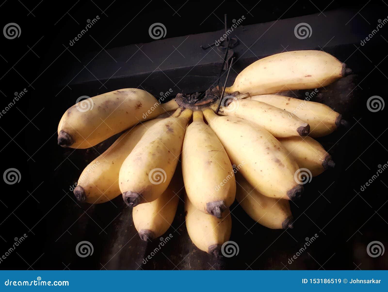 Ripe yellow bananas hanging inside a shop