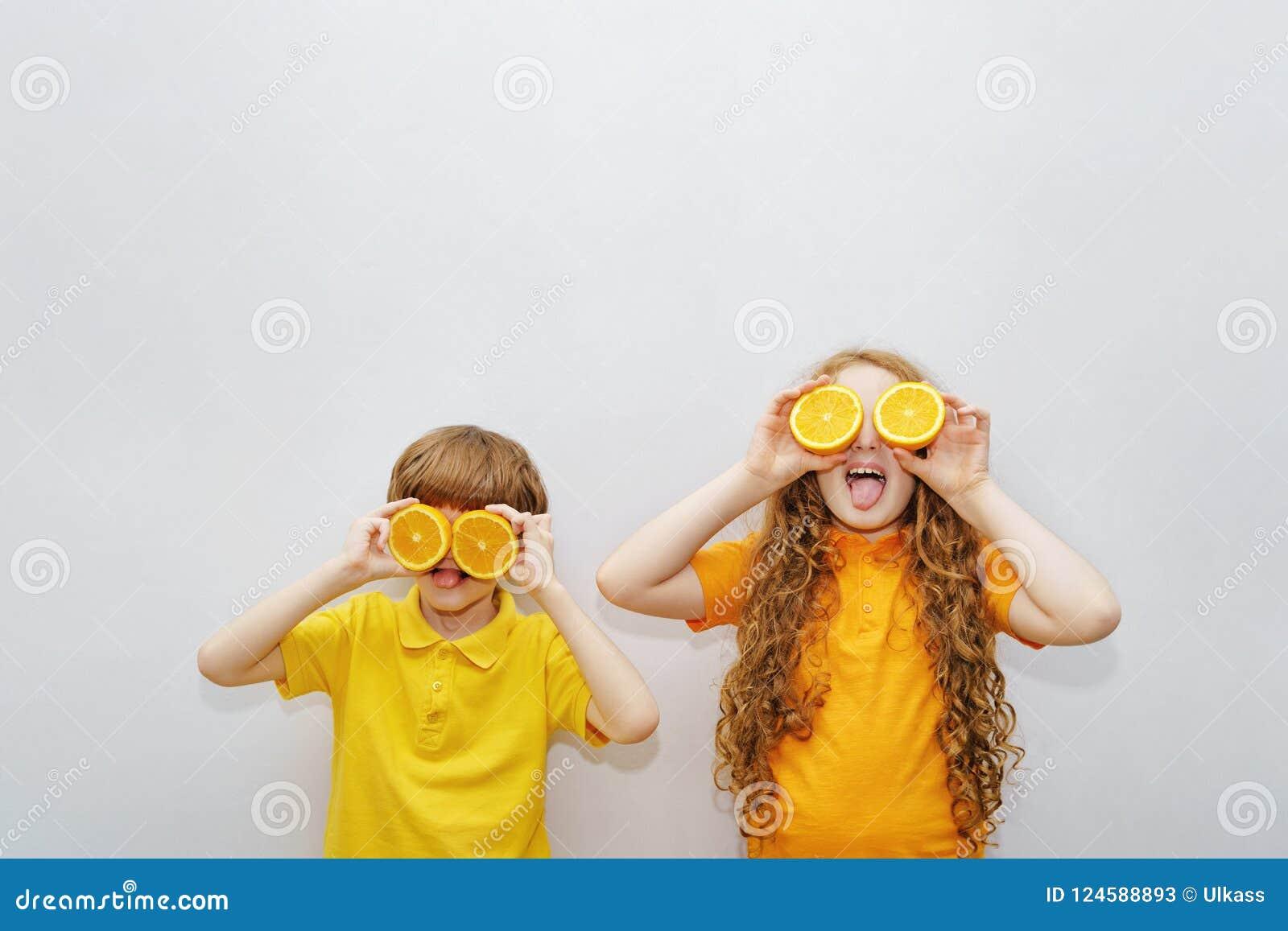 Rir crianças com olhos alaranjados mostra os dentes saudáveis brancos