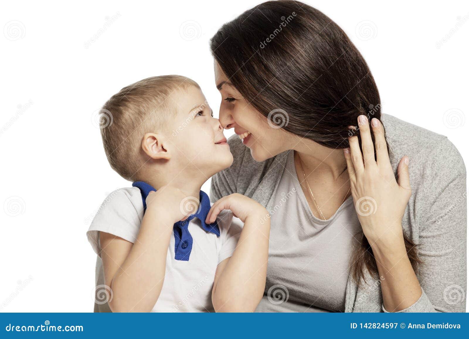 Risas y abrazos lindos del niño pequeño con la mamá, aislada en el fondo blanco Dulzura y amor