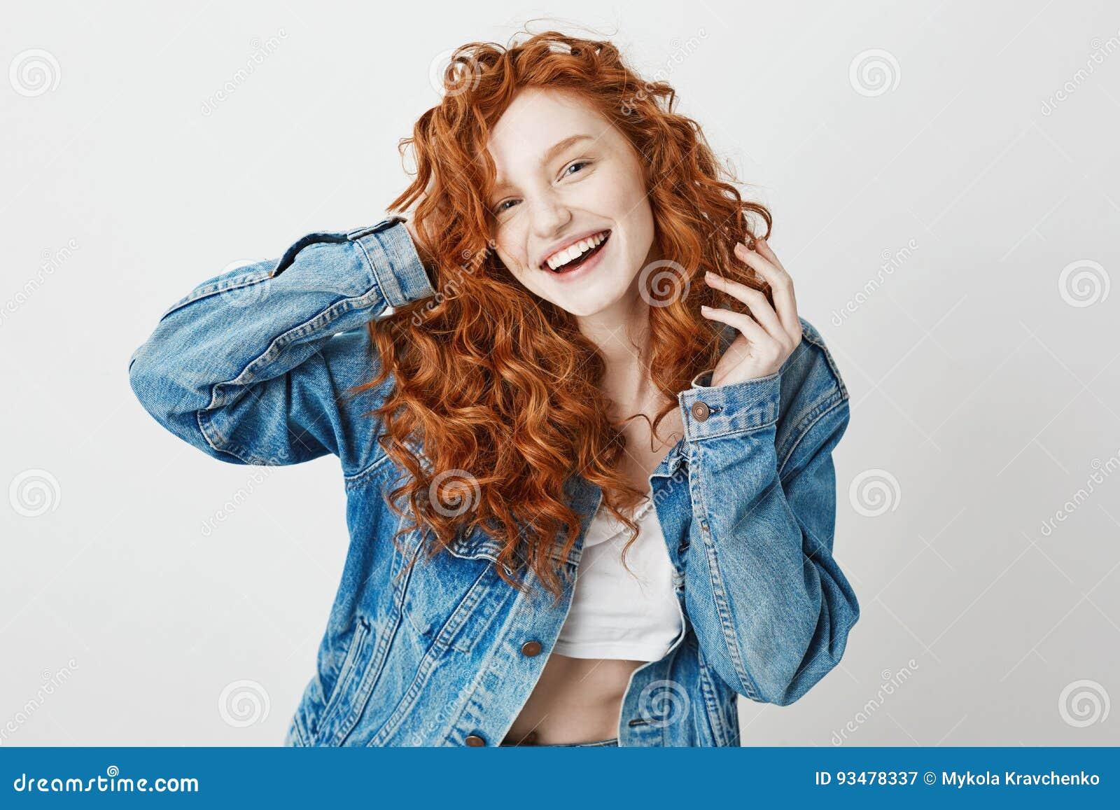 Risata sorridente della ragazza allegra della testarossa esaminando macchina fotografica sopra fondo bianco Copi lo spazio