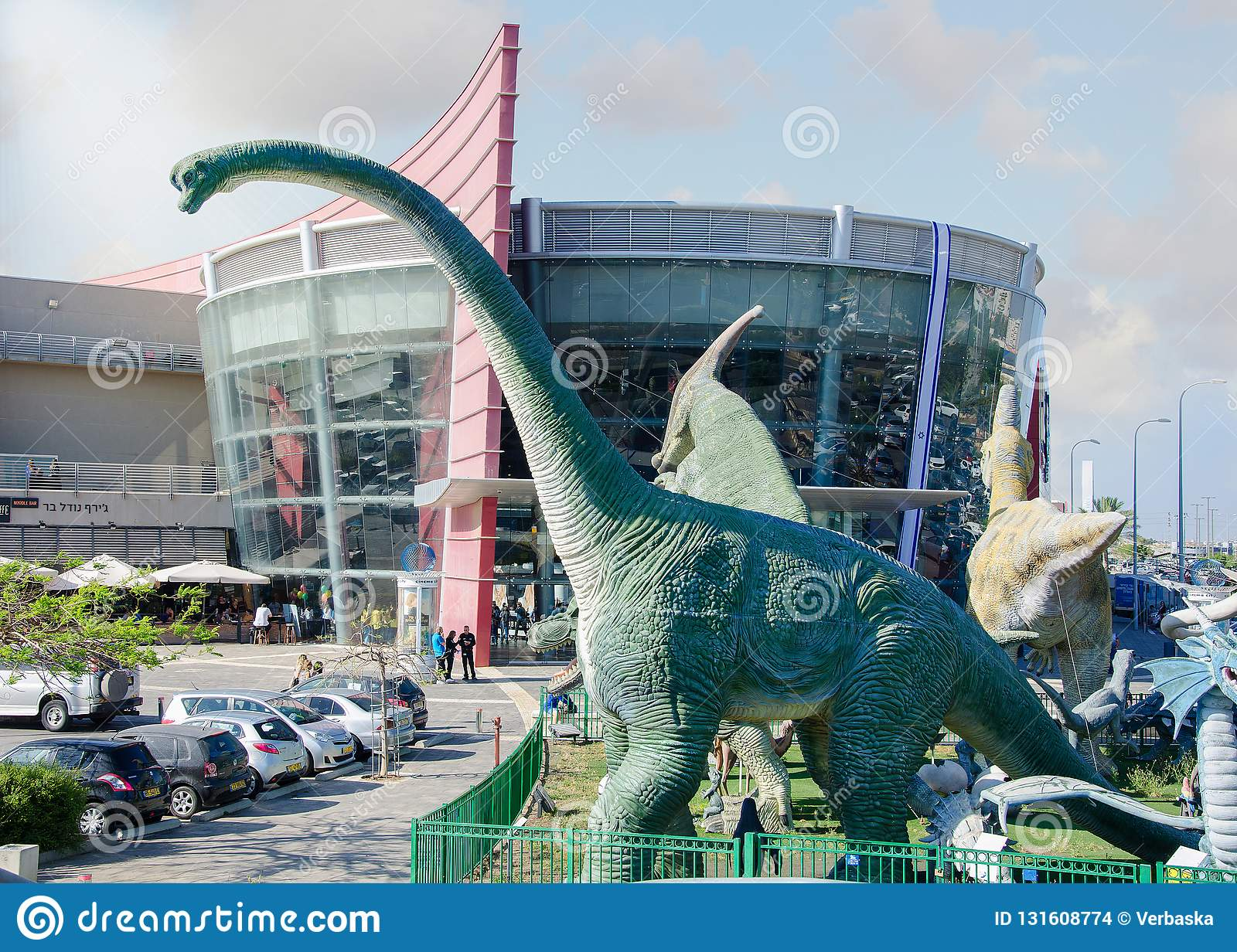 The real size sculptures of most known dinosaurs species are in the fenced ground in front of the entrance to the Cinema City.