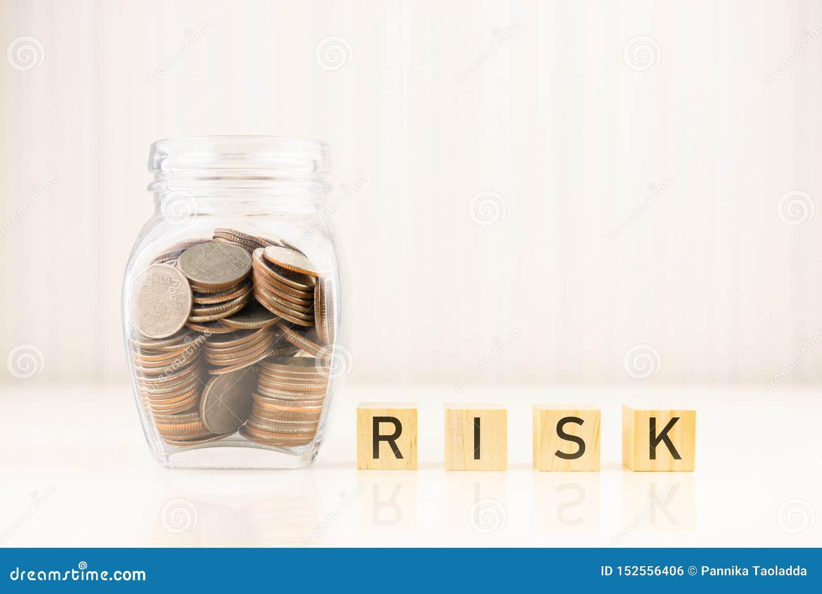 Risikomanagement-Konzept Münzen im Glas mit Würfelwort RISIKO des hölzernen Blockes