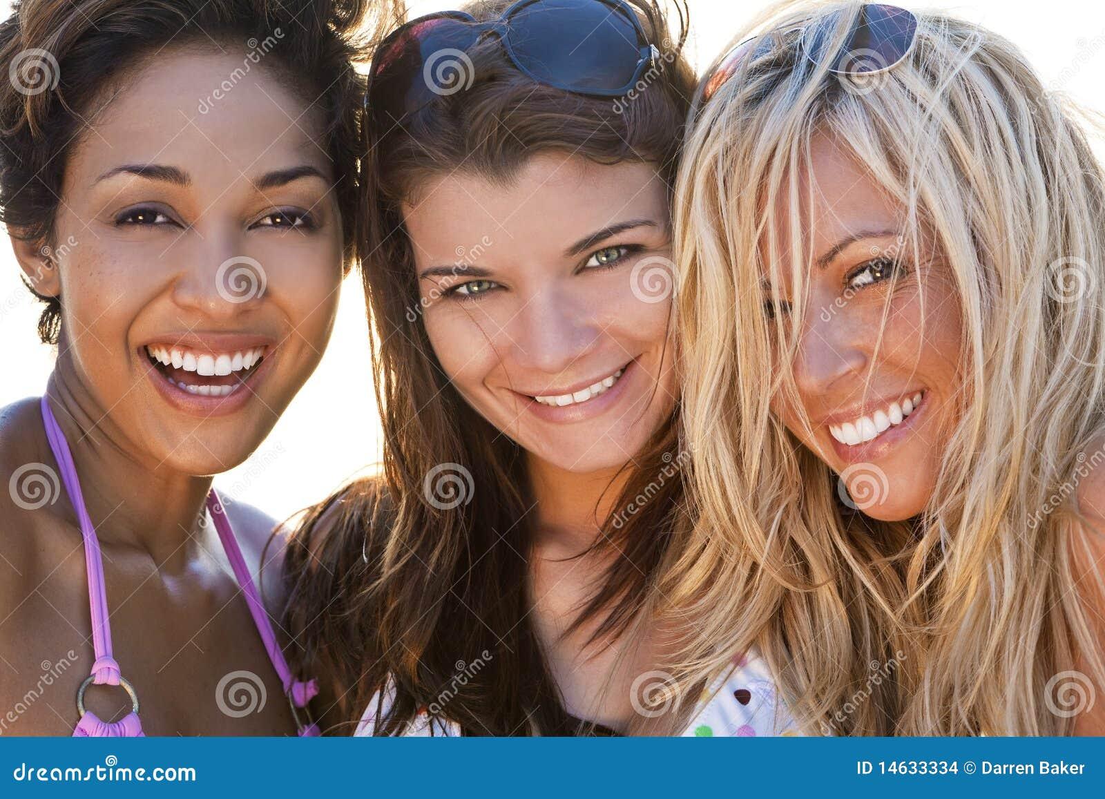 Riso bonito de três amigos das mulheres novas