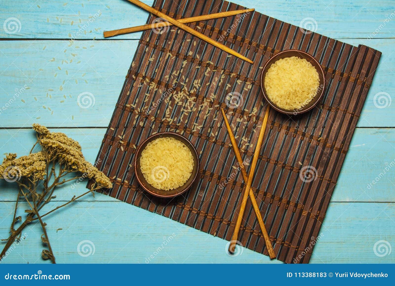 Riso giapponese in una ciotola di legno Bastoncini di legno sulla tavola di una stuoia di bambù Cucina asiatica Vista da sopra