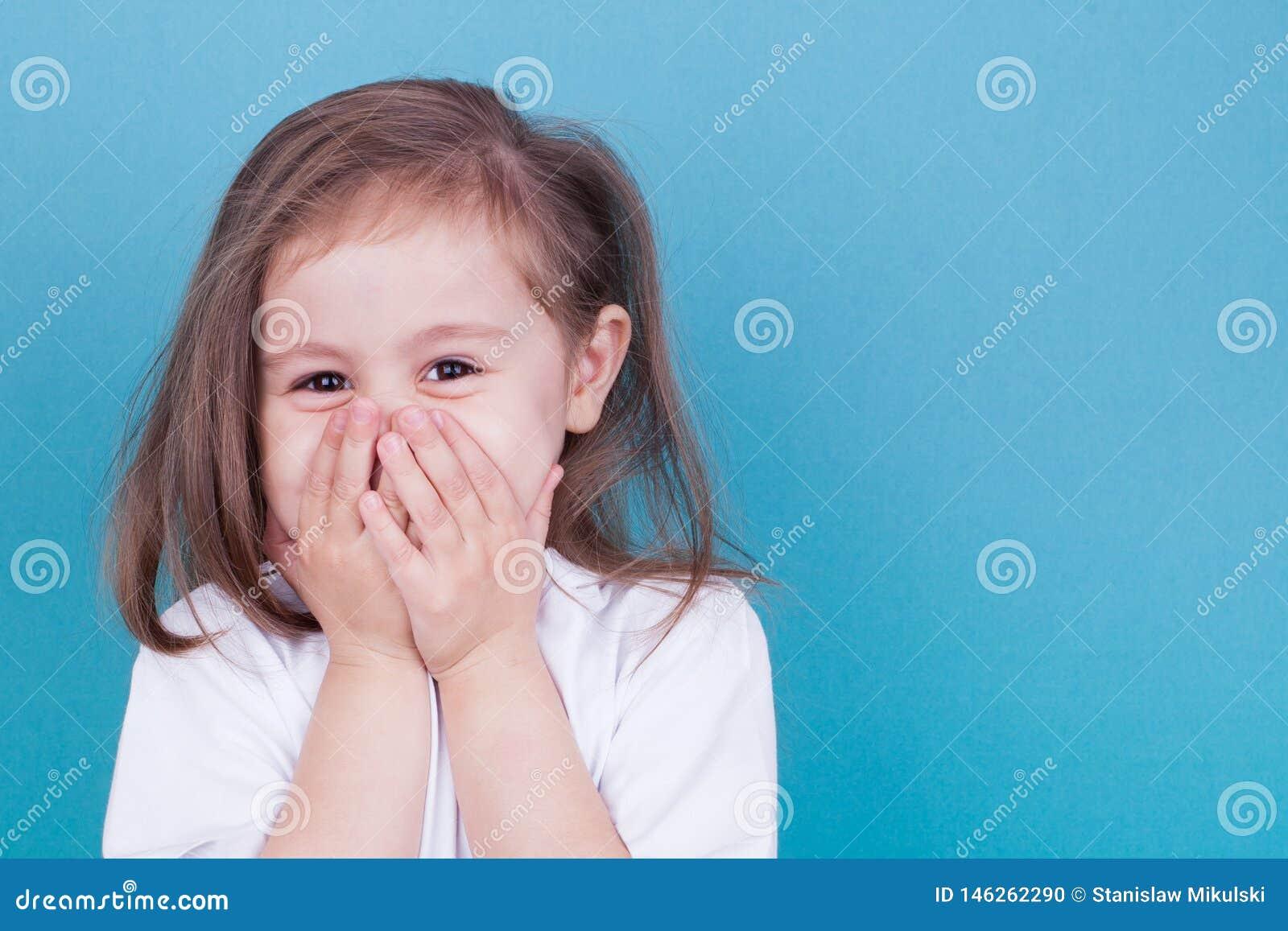 Risos da menina que cobrem sua cara com suas m?os