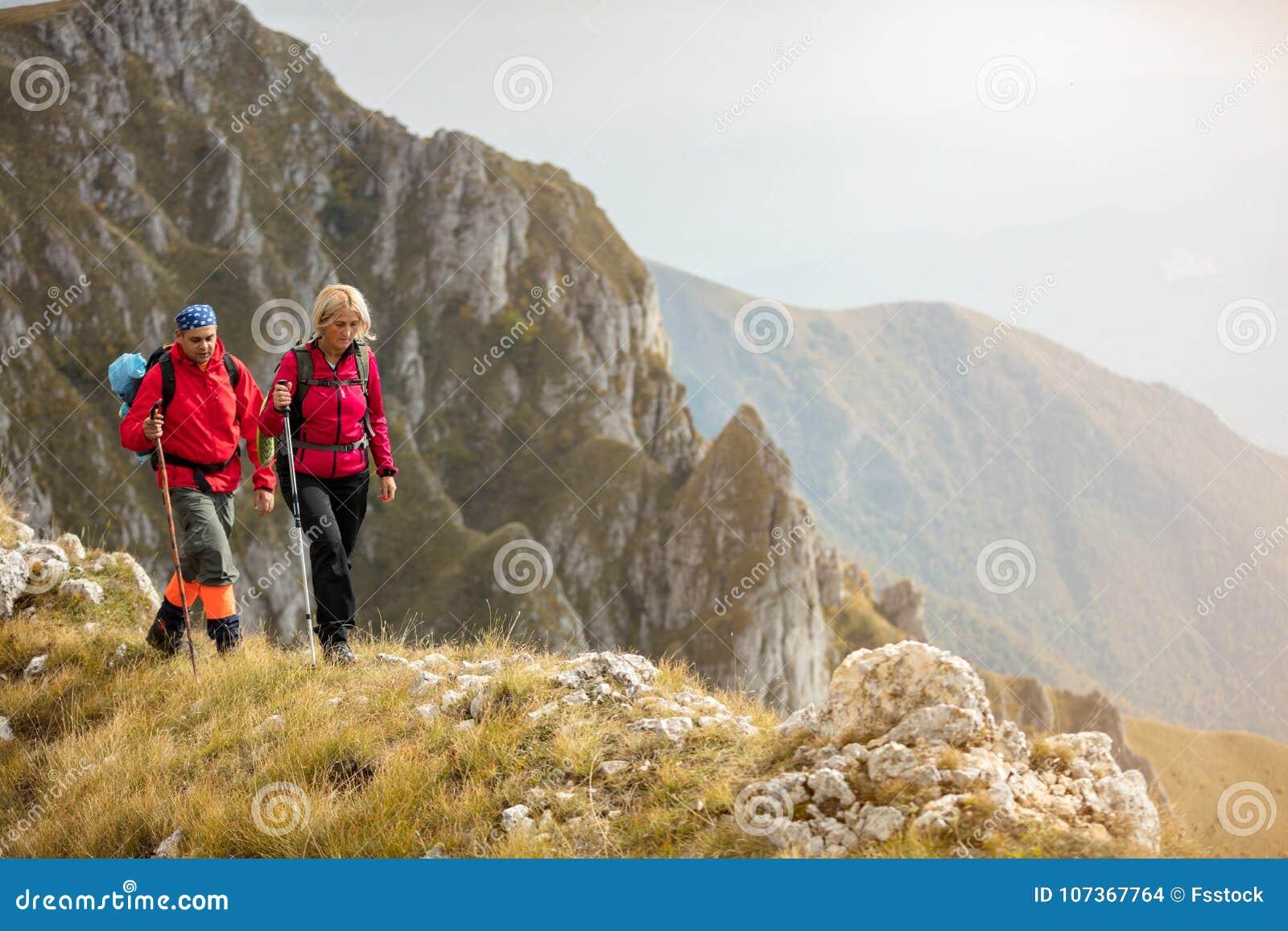 Risquez, voyagez, tourisme, hausse et concept de personnes - couple de sourire marchant avec des sacs à dos dehors