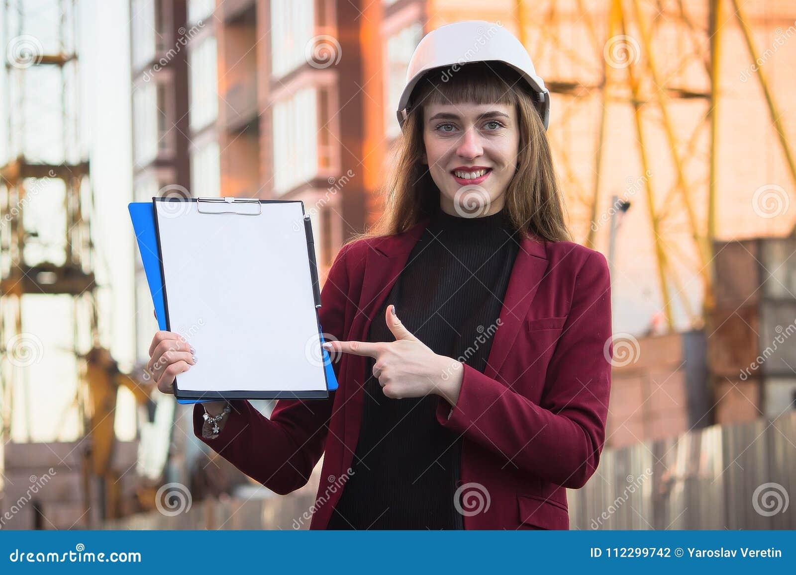 Ritningar för kvinnabyggmästareinnehav, skrivplatta Le arkitektflickan i hjälm på byggnadsbakgrund