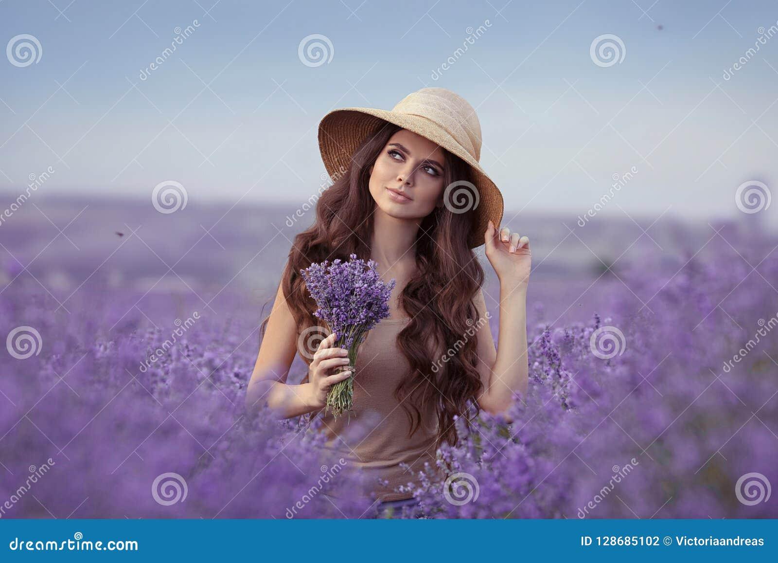 Ritratto adorabile della giovane donna in cappello di paglia sopra il  giacimento porpora della lavanda Ragazza attraente con capelli ricci lunghi  che ... 98464c9fe48c