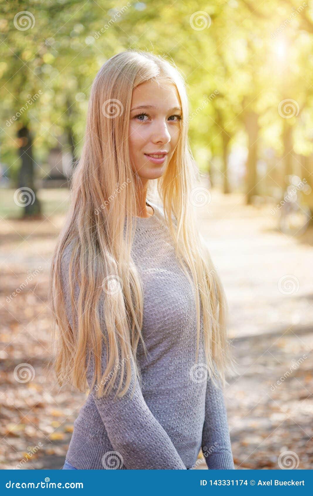 Ritratto all aperto della giovane donna bionda che gode del giorno soleggiato