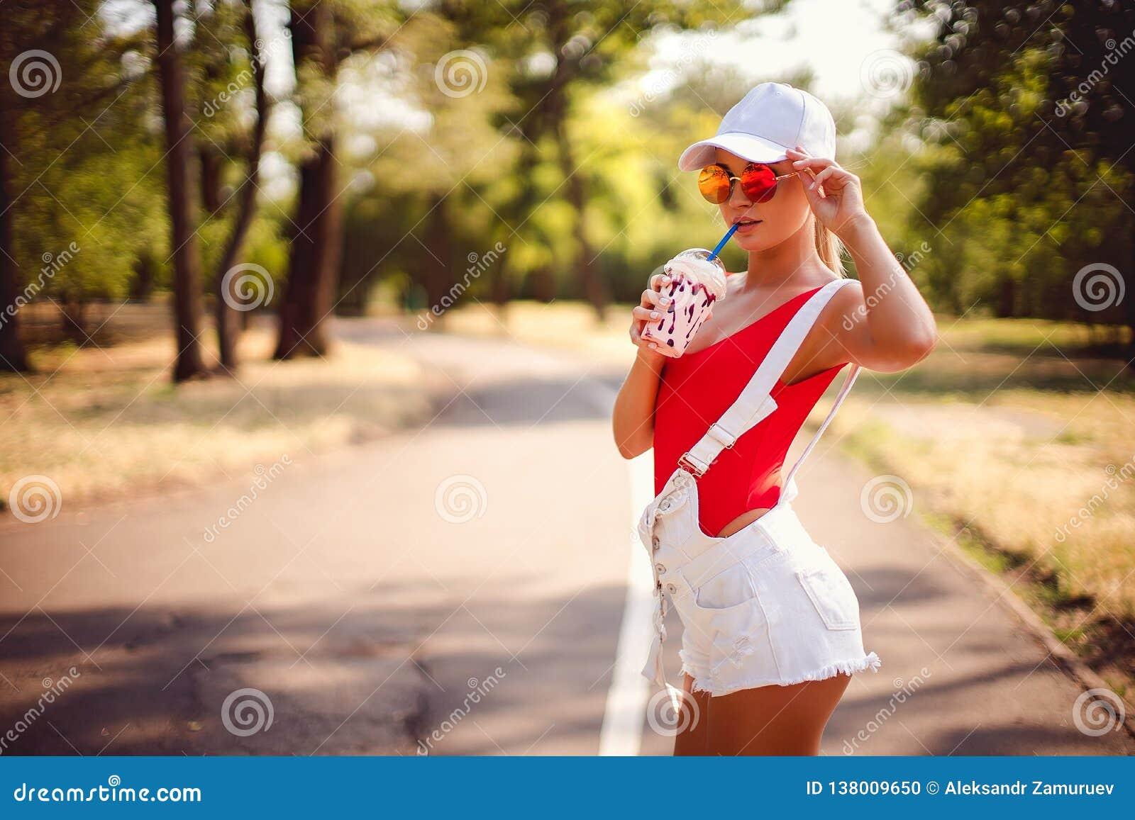 Ritratto all aperto della ragazza abbastanza alla moda di modo divertendosi frappé bevente