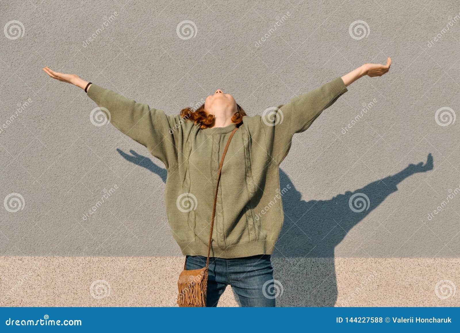 Ritratto all aperto della ragazza teenager felice con le mani su ed occhi chiusi, fondo soleggiato grigio della parete, emozione