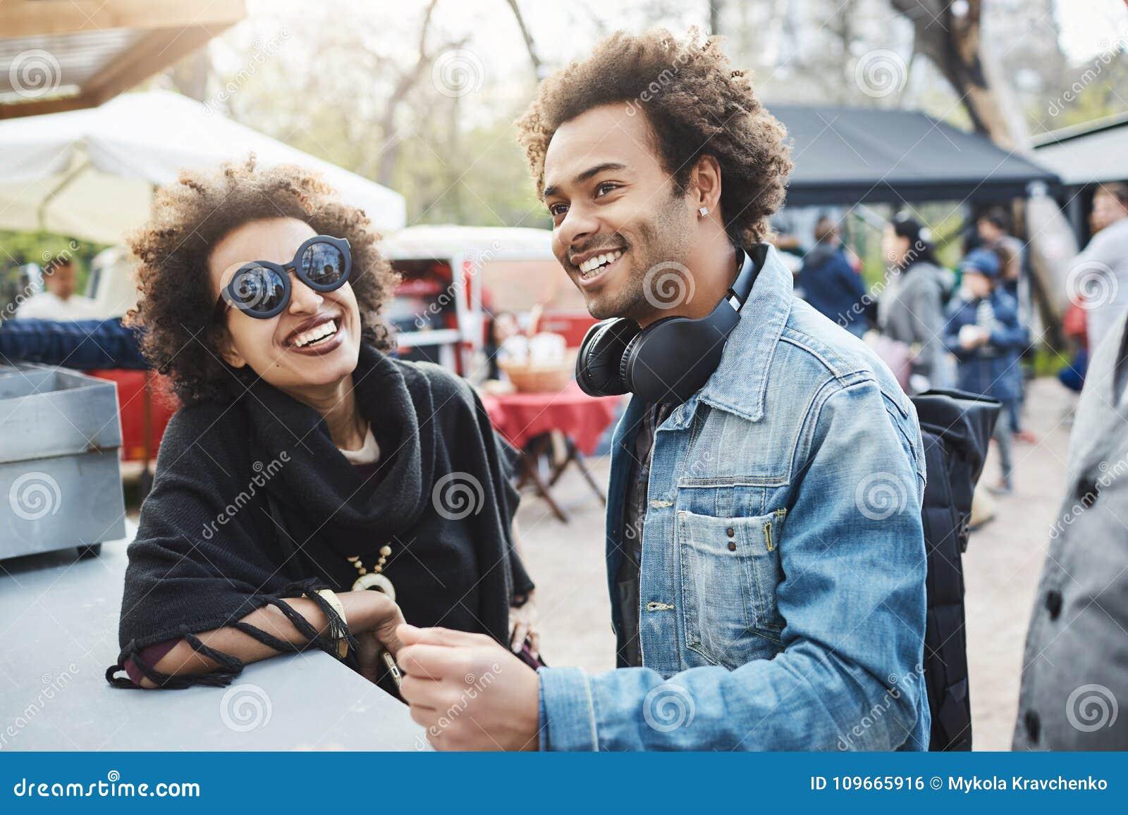 Ritratto all aperto delle coppie afroamericane felici con le acconciature di afro, appoggiantesi tavola mentre sul festival dell