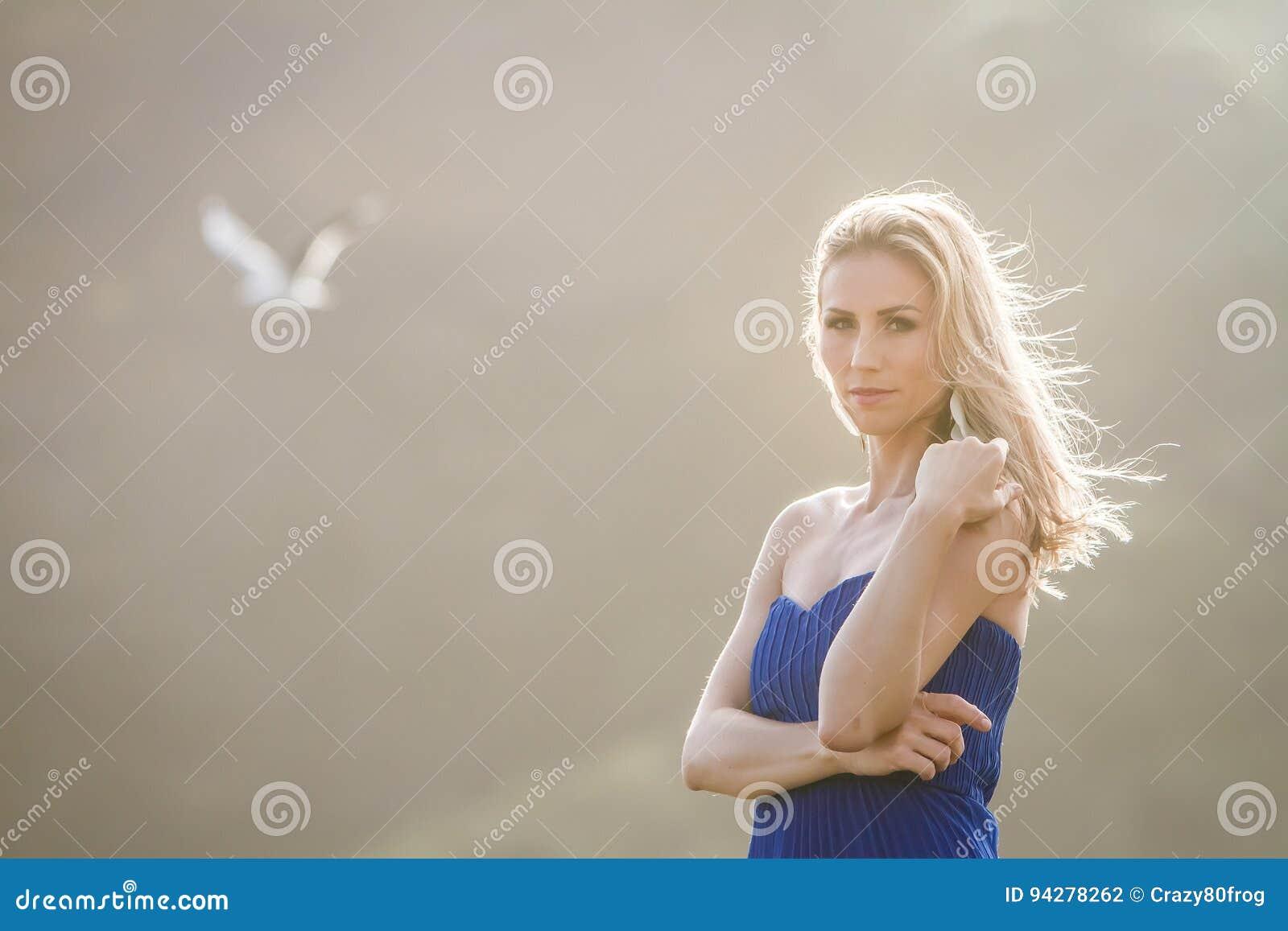 Ritratto all aperto di giovane bella donna in abito blu che posa sopra