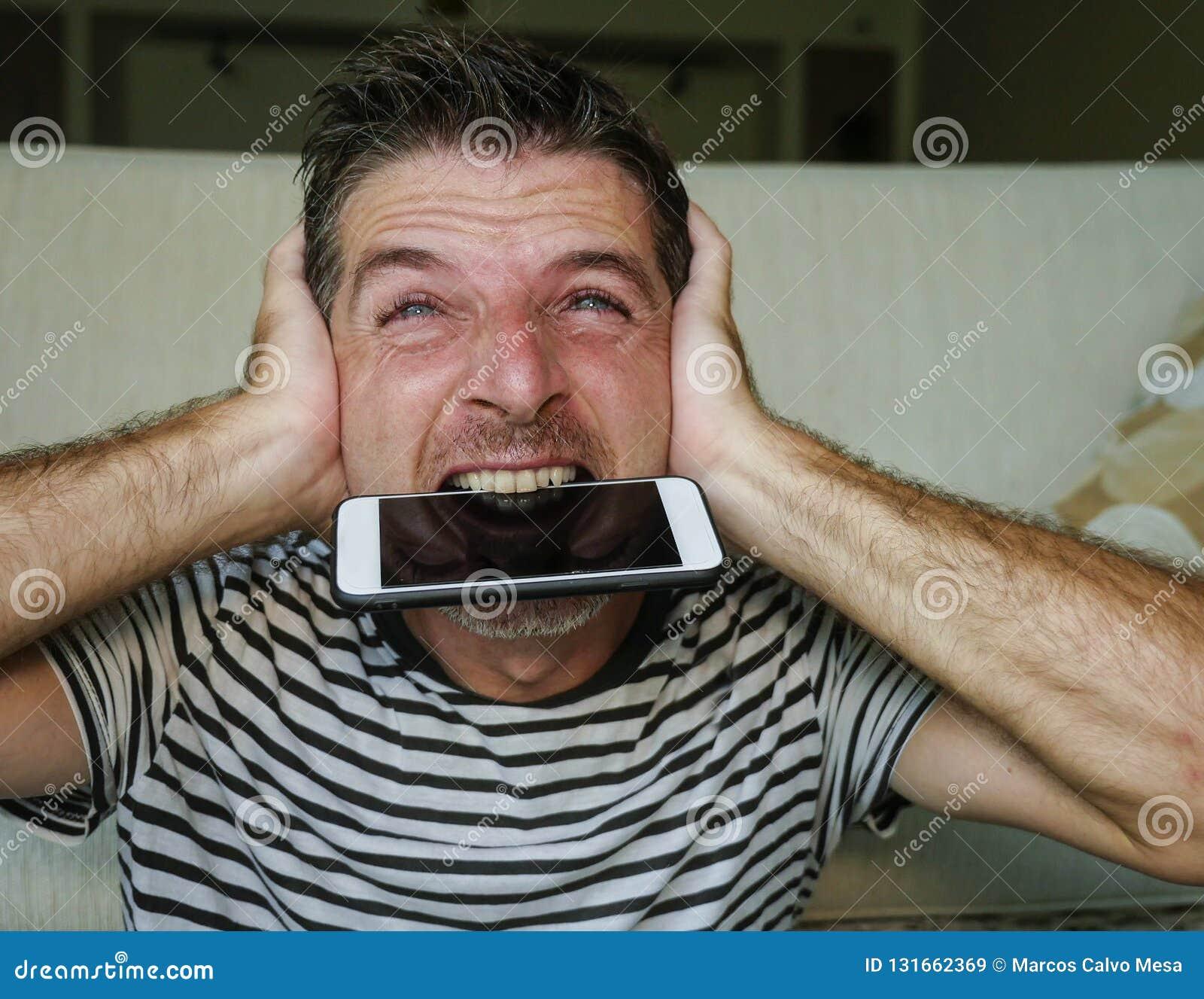 Ritratto alto vicino del fronte di giovane telefono cellulare mordente attraente e sollecitato dell uomo disperato ed ansioso in
