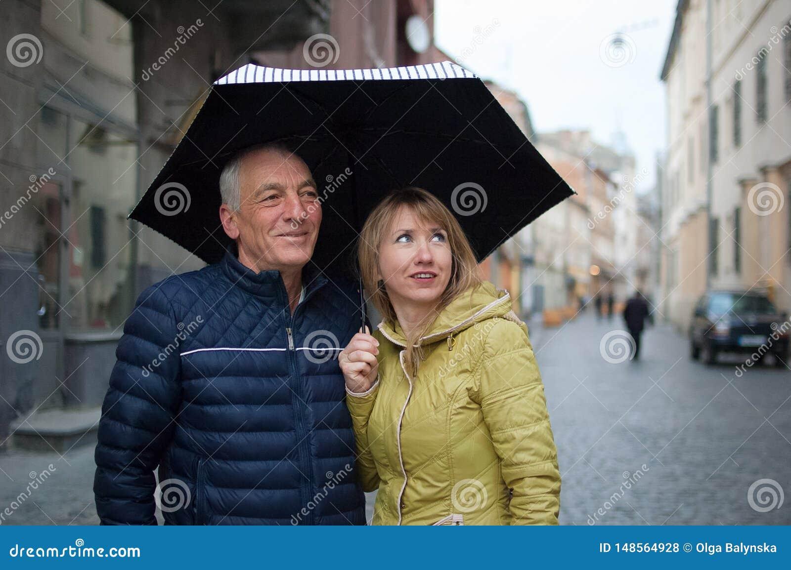 Ritratto alto vicino dell uomo anziano e sua giovane della moglie bionda-dai capelli che si abbracciano e che stanno sotto il lor
