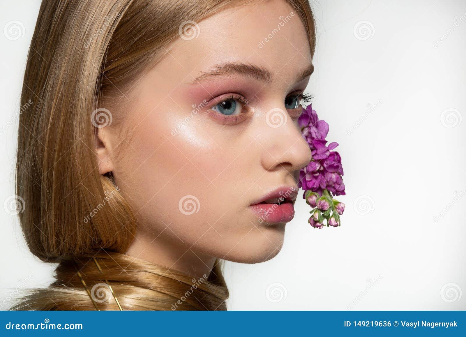 Ritratto alto vicino della ragazza con gli occhi azzurri, trucco luminoso, collo avvolto in capelli, fiori porpora arricciati in