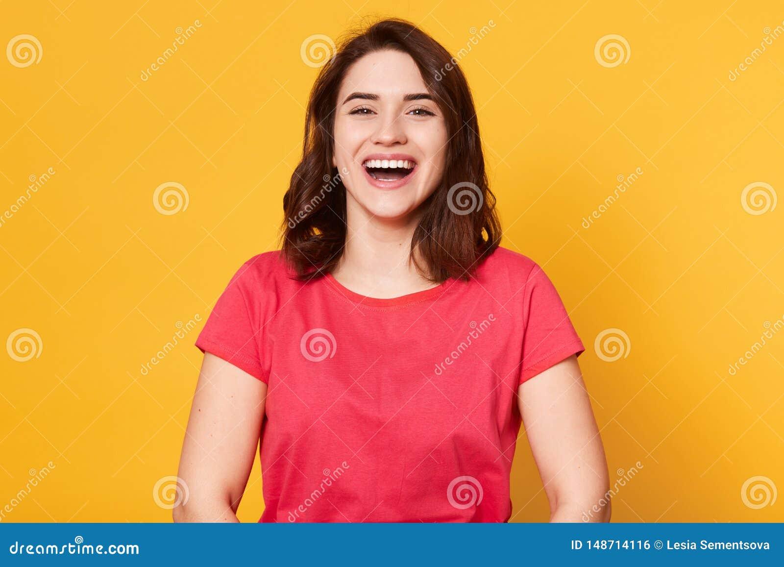 Ritratto alto vicino di bella ragazza mora sveglia nel buon umore che porta maglietta rossa casuale, ridendo, godente del tempo p