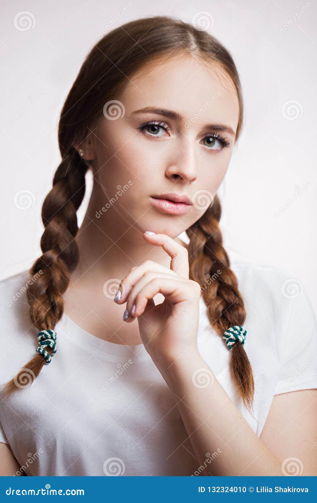 Ritratto alto vicino di bella ragazza sensuale su fondo bianco Donna attraente con i cigli lunghi e la pelle pulita, trecce