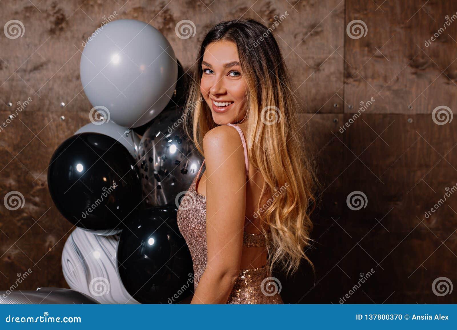 Ritratto alto vicino di bella signora sorridente con capelli lunghi biondi che portano sparcly vestito che esamina macchina fotog