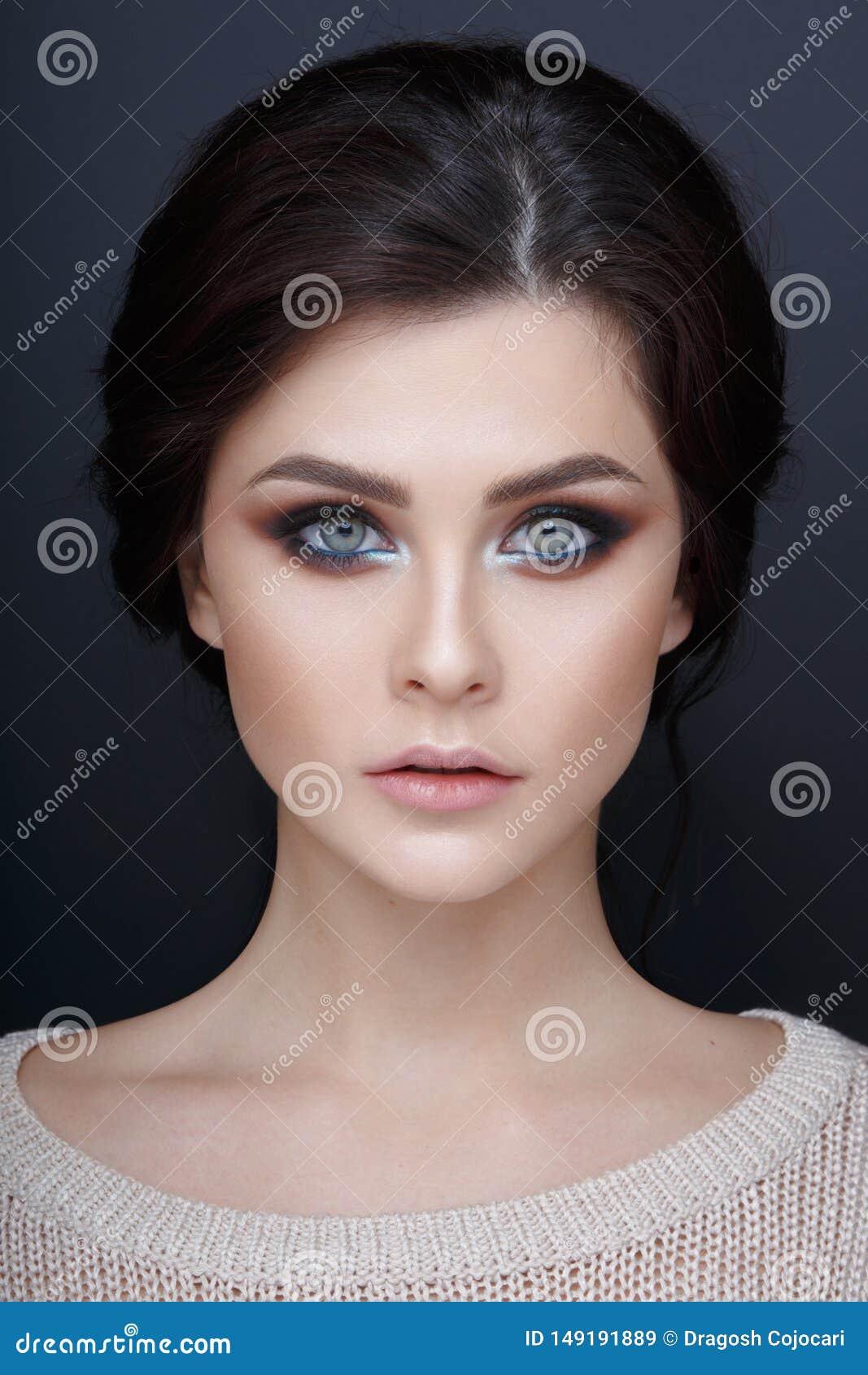 Ritratto alto vicino di una ragazza beautyful con trucco perfetto Fronte di bella ragazza, su un fondo grigio