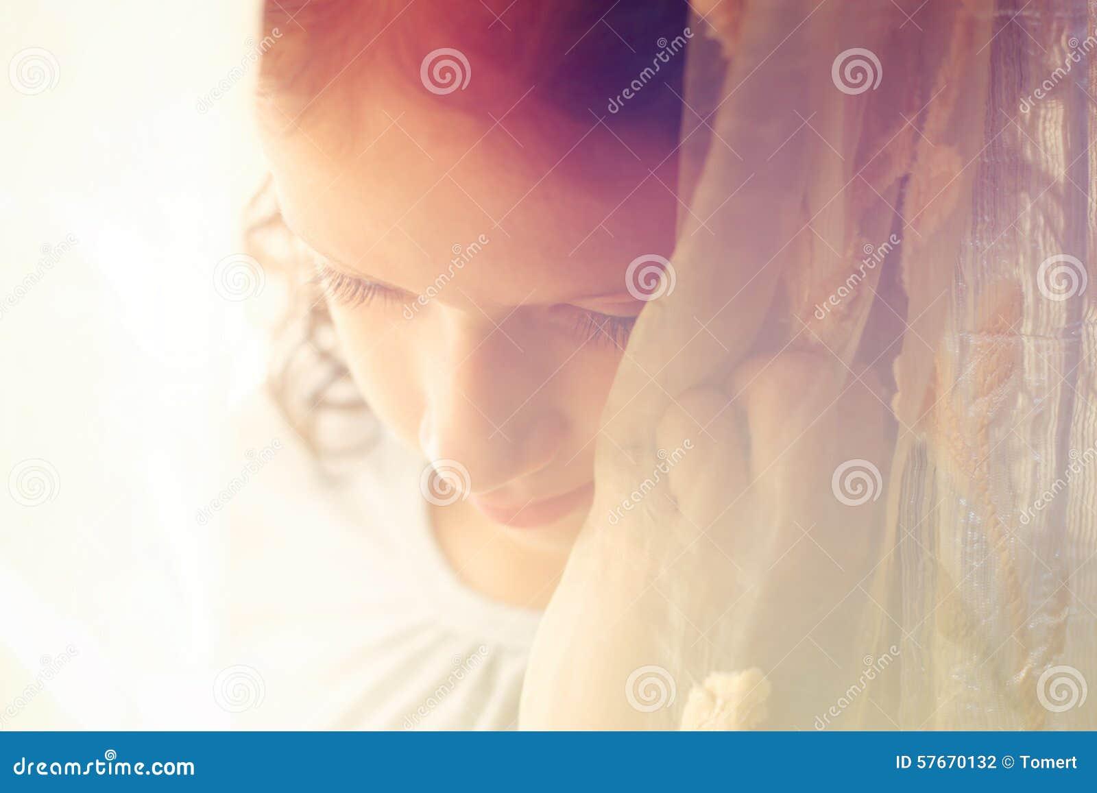 Ritratto astratto della bambina premurosa vicino alla finestra retro immagine filtrata
