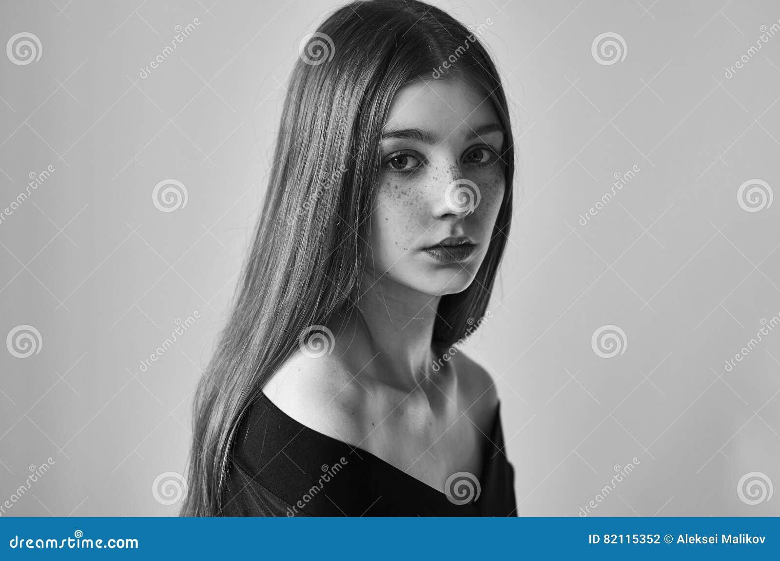 Ritratto in bianco e nero drammatico di bella ragazza sola con le lentiggini su un fondo bianco nel colpo dello studio