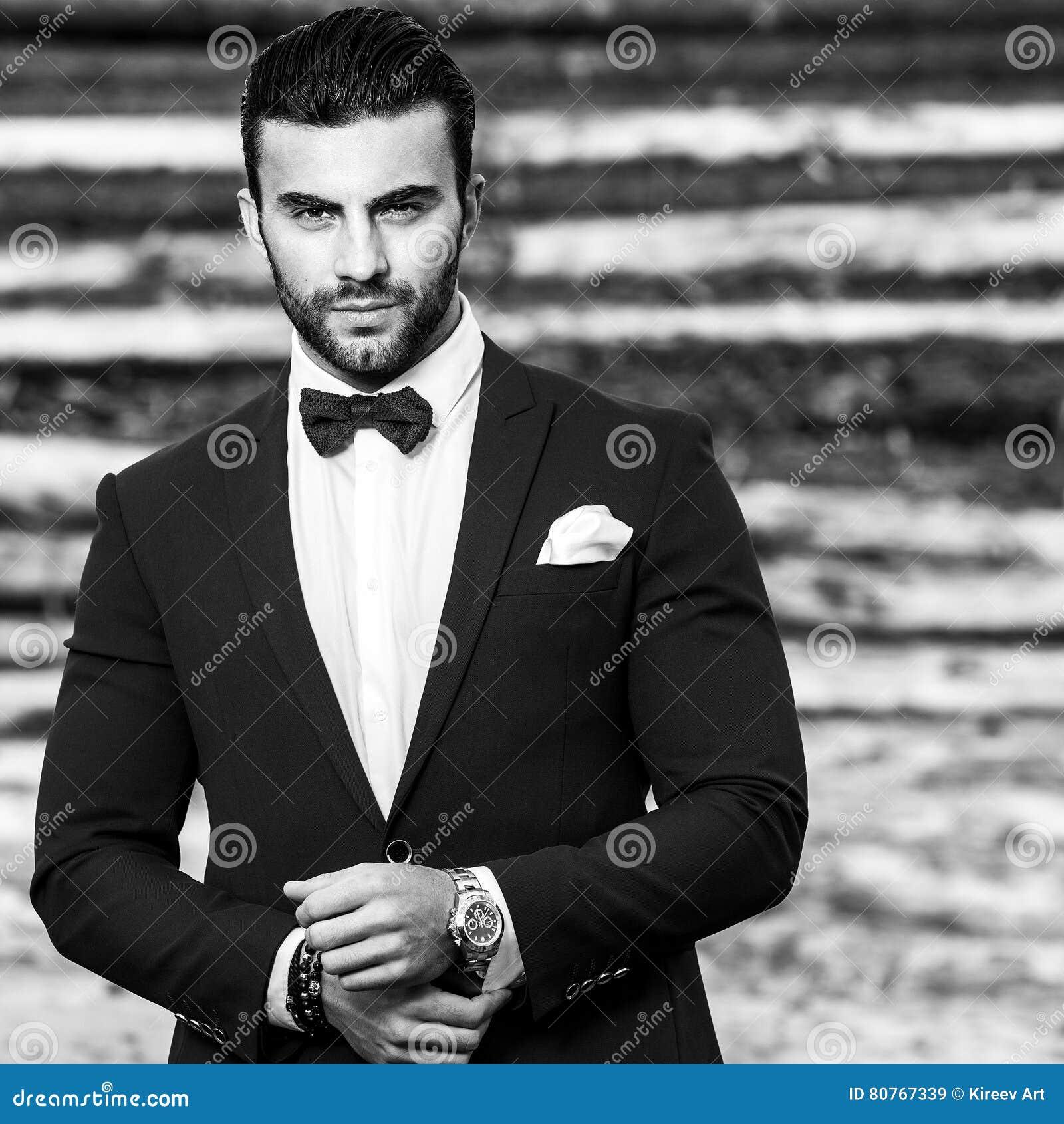 Ritratto bianco Nero di bello uomo alla moda in vestito alla moda contro  fondo di legno 37a5d5a3c07