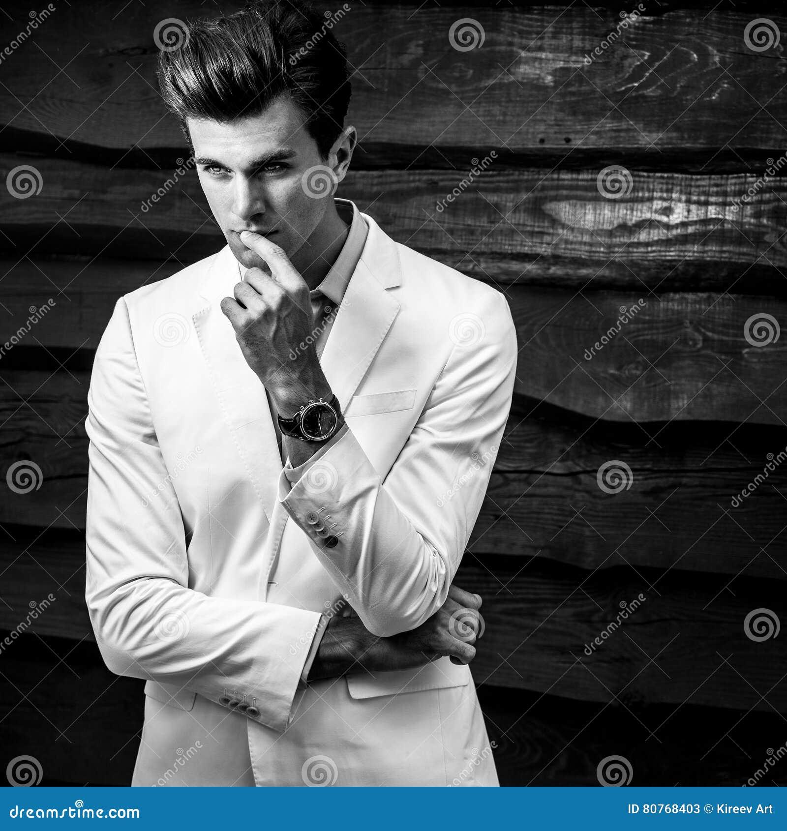 Ritratto bianco Nero di giovane uomo alla moda bello in vestito bianco  contro la parete di ea5f42f2bbb