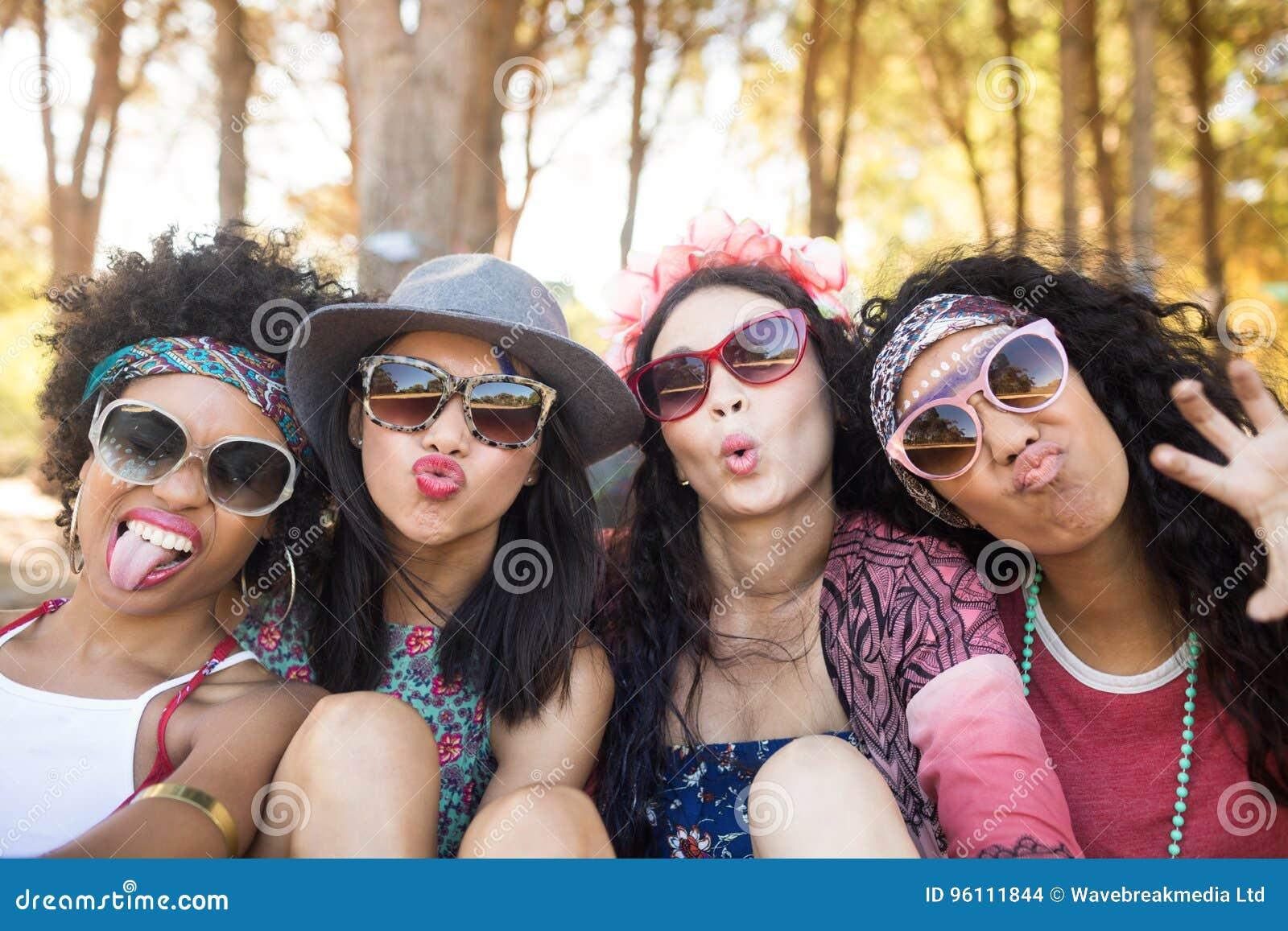 Ritratto degli amici femminili felici che fanno i fronti al campeggio