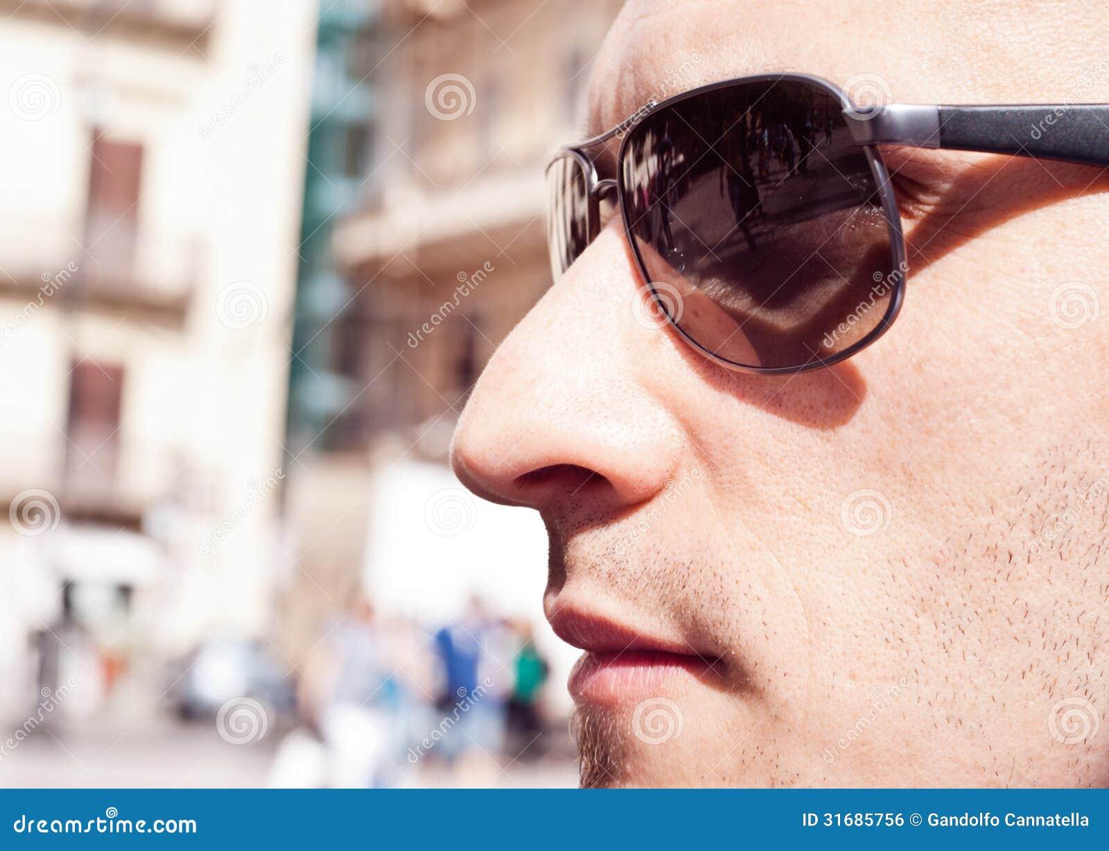 Ritratto degli occhiali da sole d uso di un tipo splendido attraente