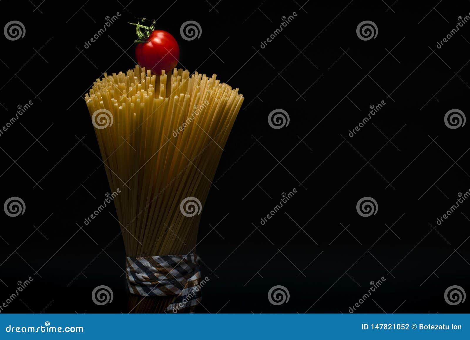 Ritratto degli spaghetti imballati di modo legati con il nastro su fondo scuro con il pomodoro sulla cima
