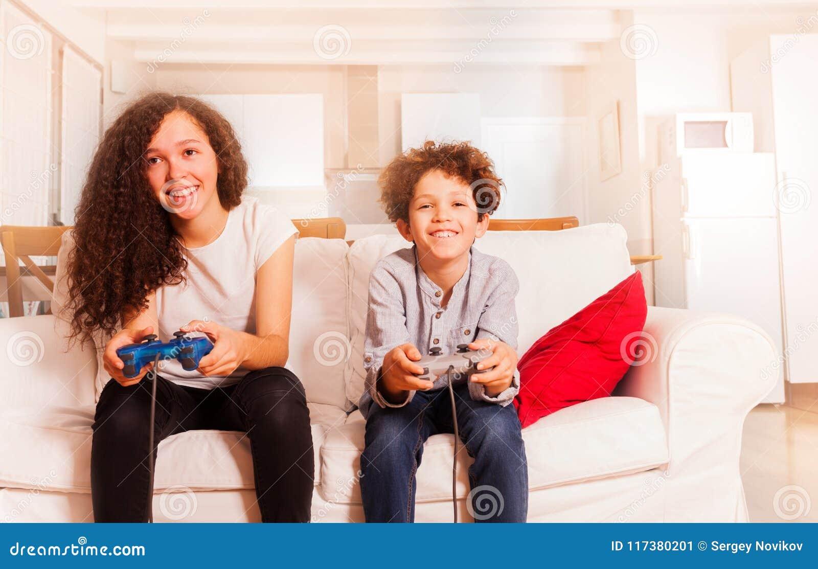 Ritratto dei bambini felici che giocano i video giochi