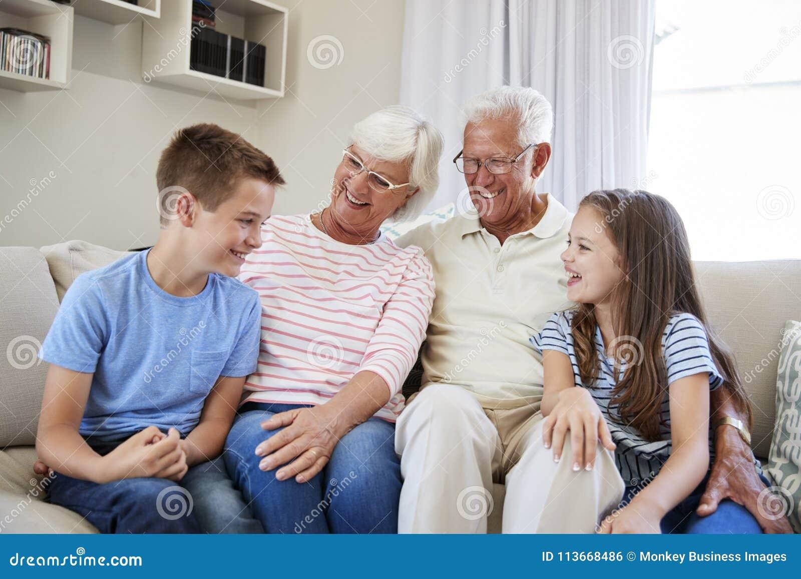 Ritratto dei nipoti che si siedono su Sofa With Grandparents
