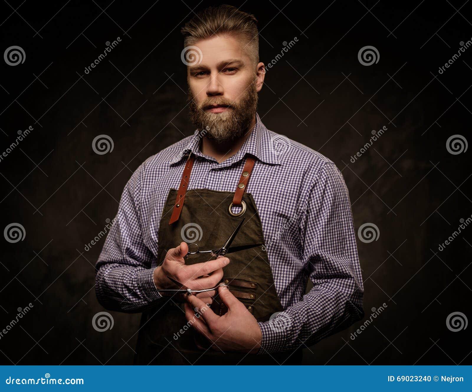 Ritratto del barbiere alla moda con la barba e degli strumenti professionali su un fondo scuro