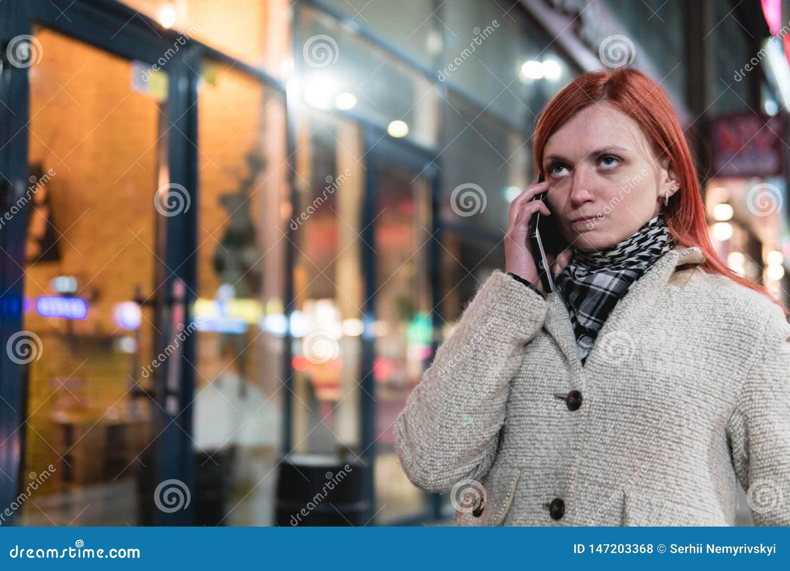 Ritratto del cellulare della tenuta della giovane donna in mani sulla via di estate, esaminante espressione irritata, rabbia, irr
