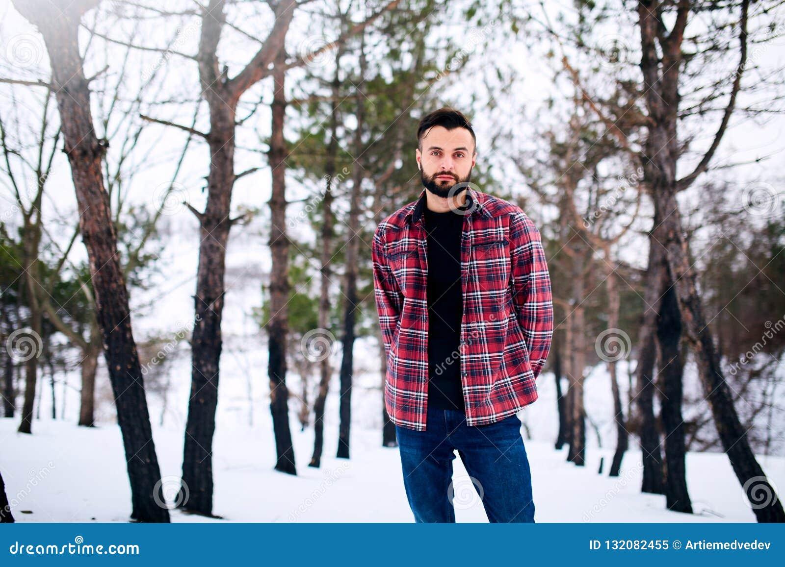 Ritratto del giovane barbuto bello nella condizione rossa della camicia di plaid nell uomo alla moda della foresta nevosa di inve