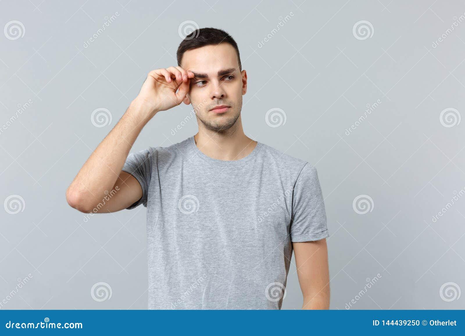 Ritratto del giovane gridante insoddisfatto in abbigliamento casual che guarda da parte, tenente mano vicino all occhio isolato s