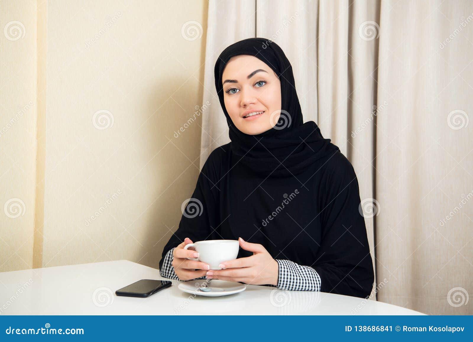 Ritratto del hijab d uso della donna asiatica attraente che gode del caffè e che sorride alla macchina fotografica