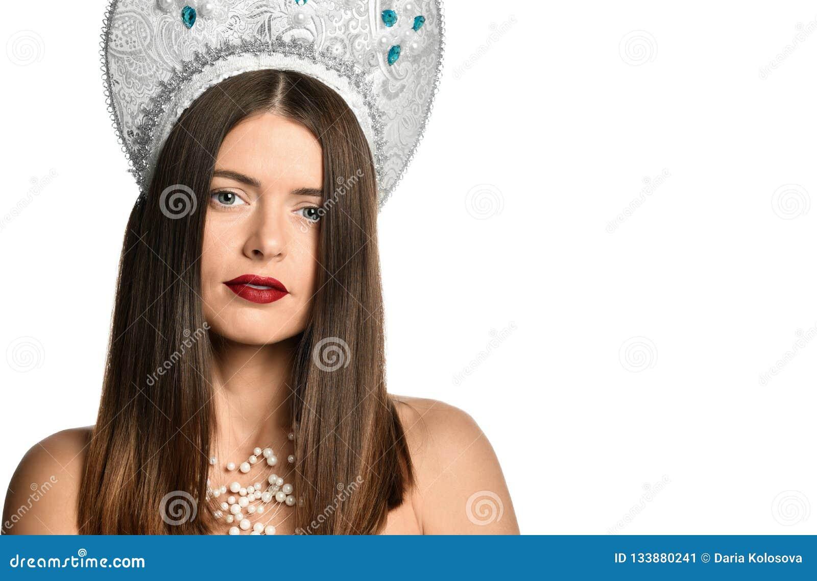 Ritratto del modello della ragazza in cappello del kokoshnik con trucco naturale e capelli di salto lunghi isolati esaminando mac
