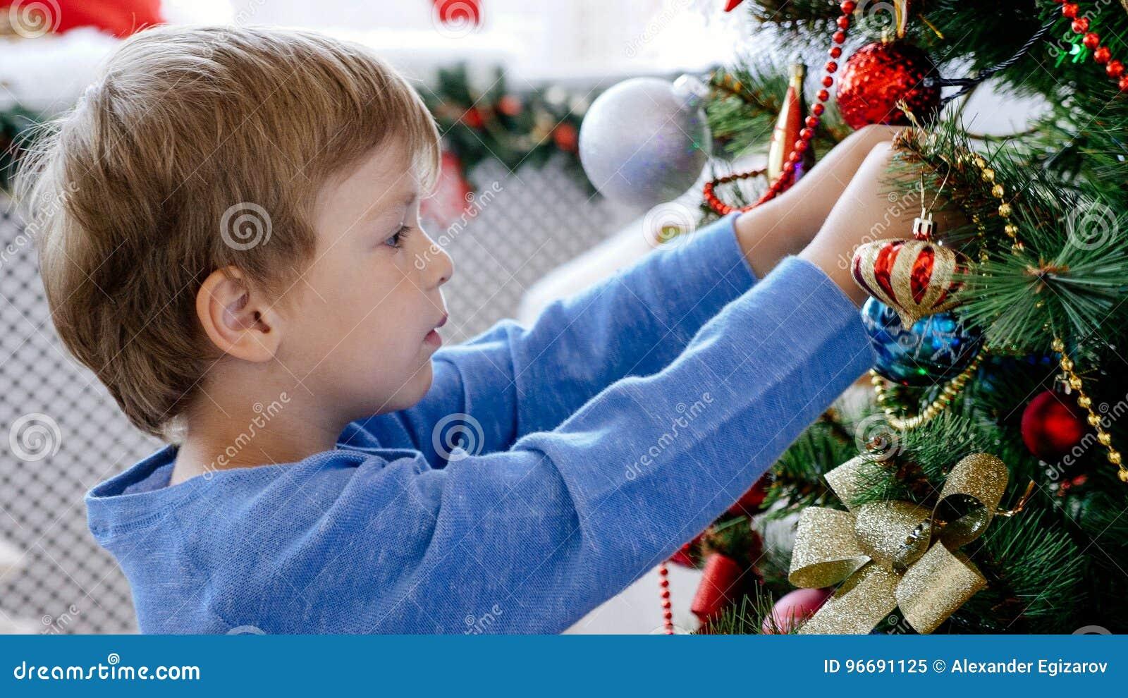 Ritratto del primo piano del bambino che decora l albero di Natale, primo piano