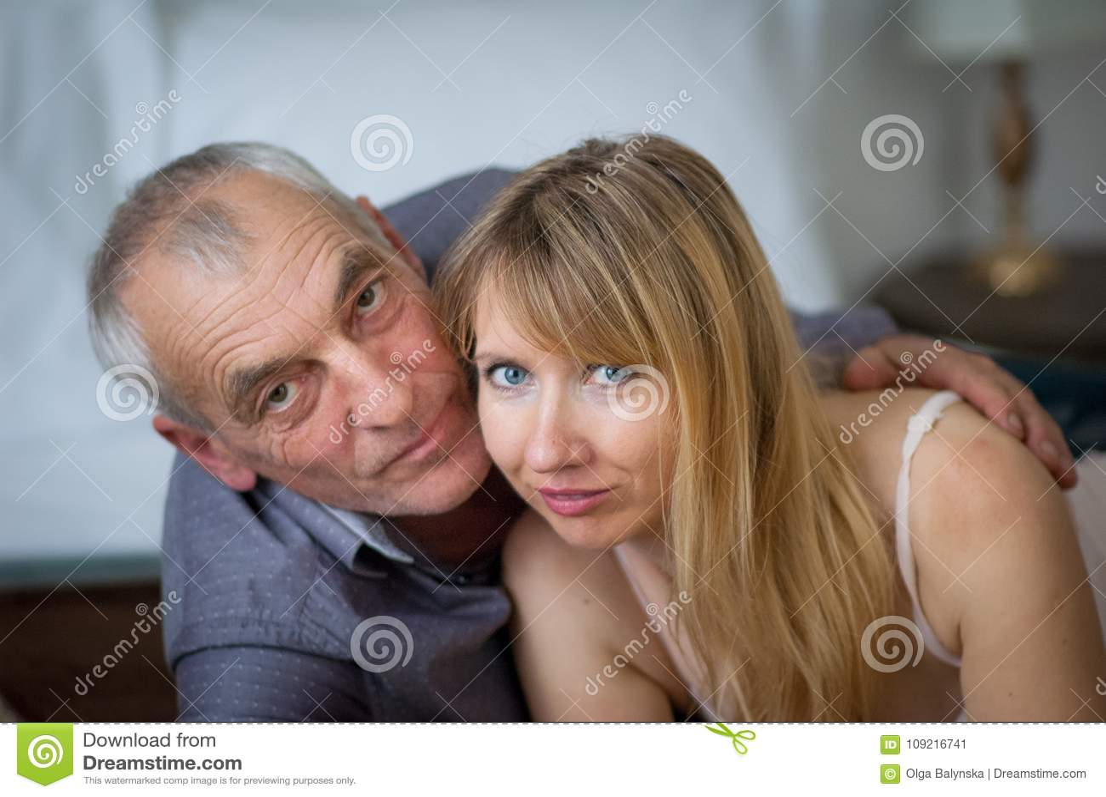 Ritratto del primo piano dell uomo anziano che abbraccia la sua giovane moglie in biancheria sexy che si trova a letto nella loro