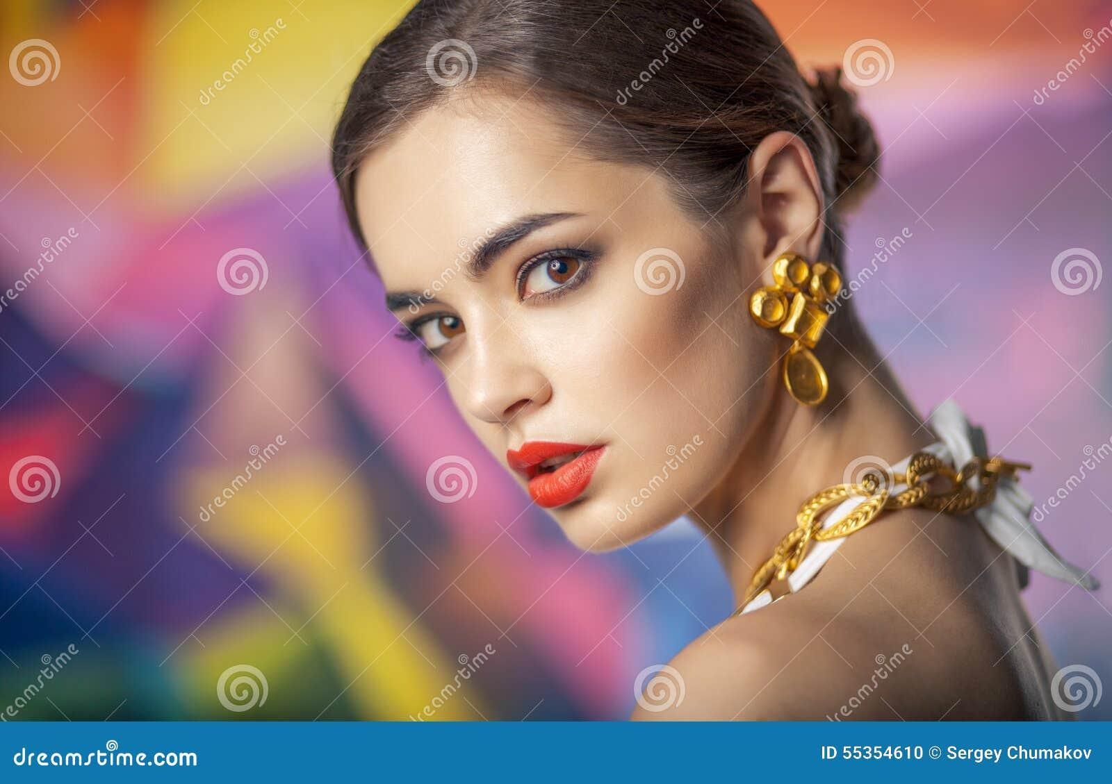 Ritratto del primo piano di bella donna caucasica su backgr variopinto