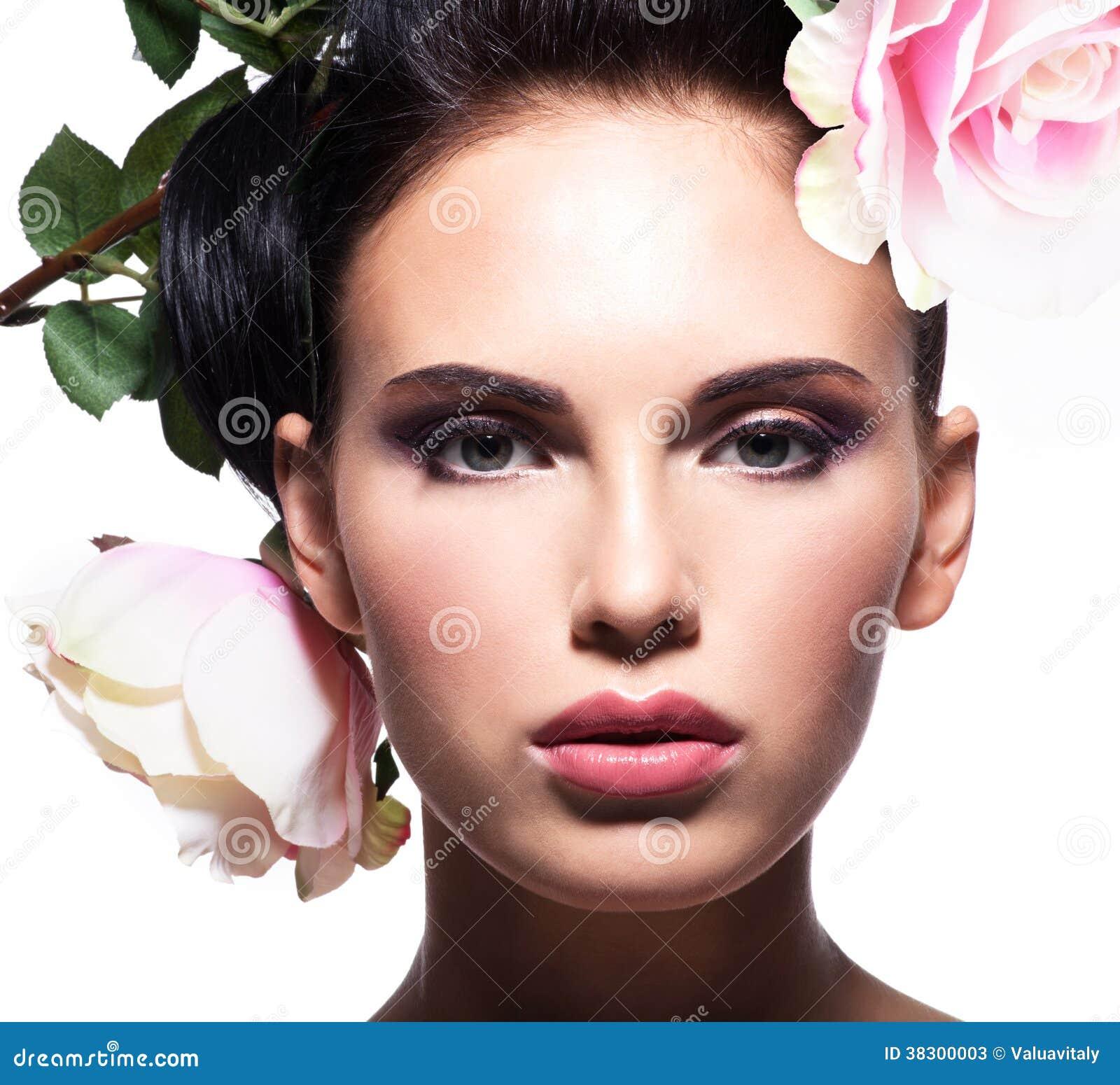 Ritratto del primo piano di bella donna con i fiori rosa in capelli