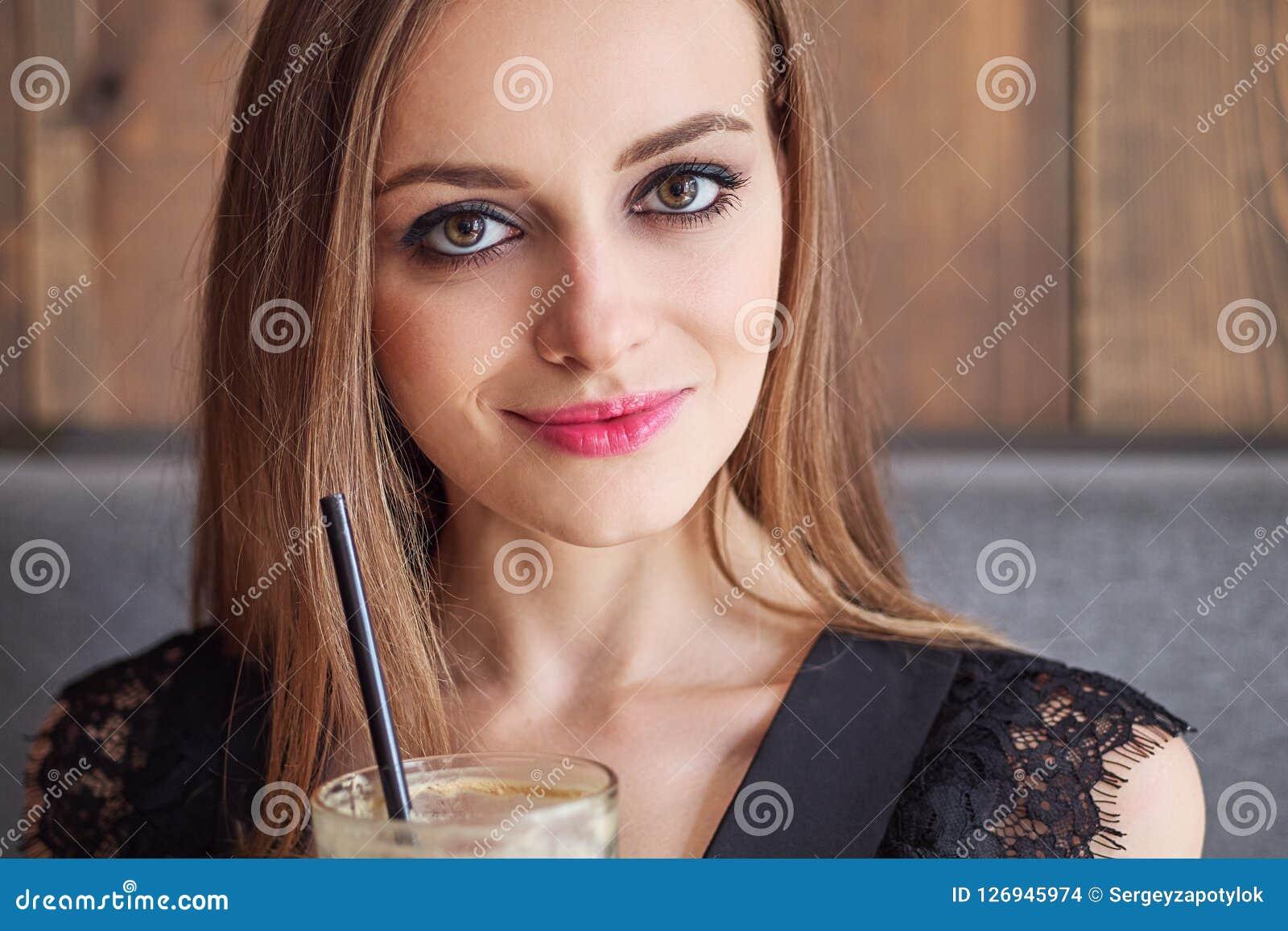 Ritratto del primo piano di giovane donna adorabile con trucco d avanguardia degli occhi splendidi che beve grande tazza di caffè