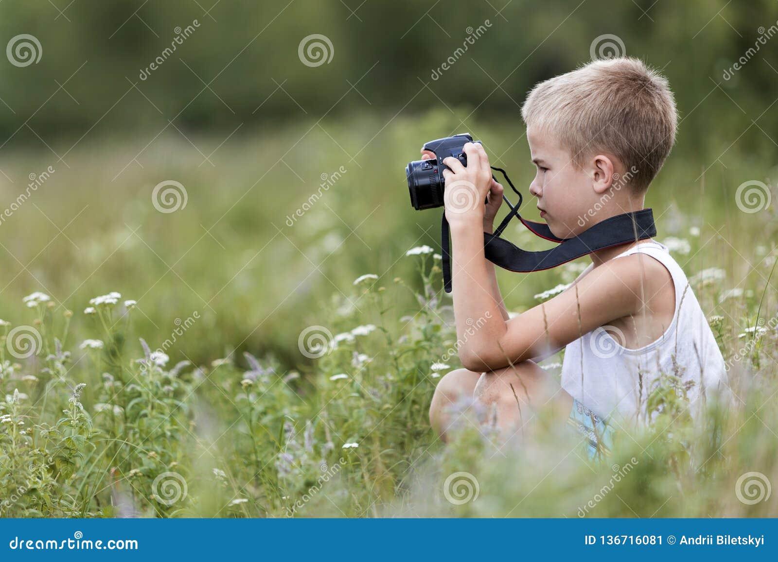 Ritratto del primo piano di profilo di giovane ragazzo bello sveglio biondo del bambino con la macchina fotografica che prende le
