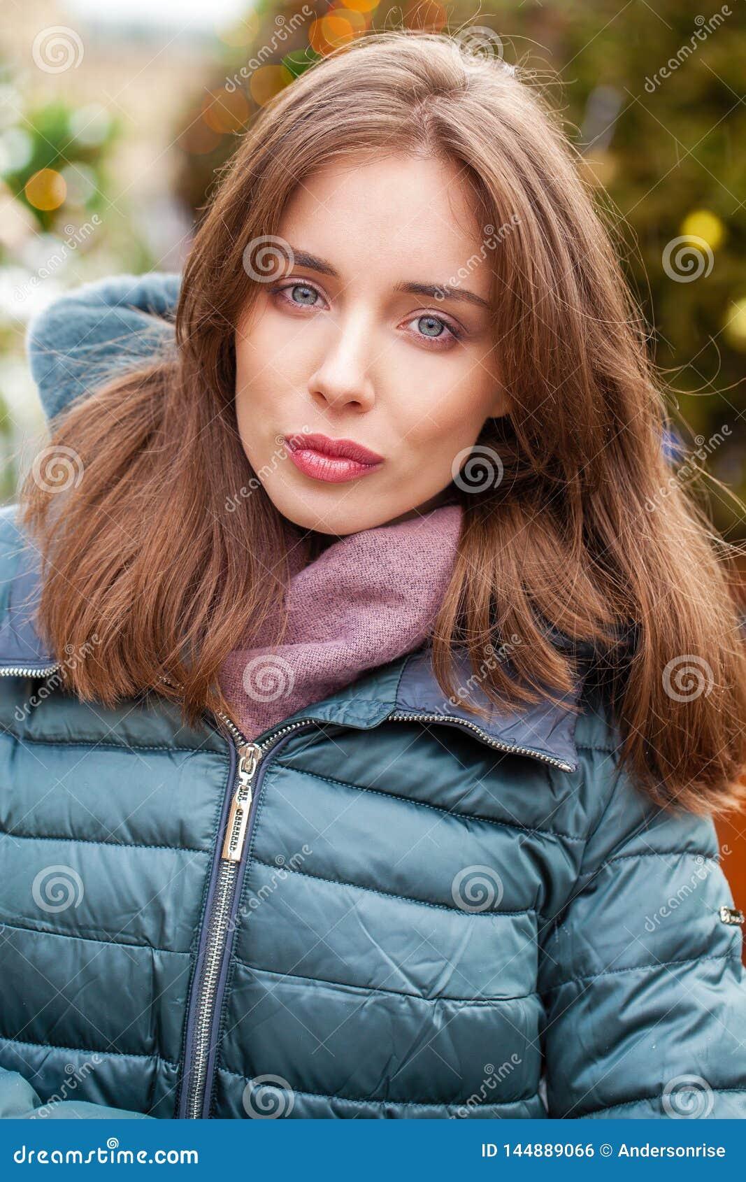 Ritratto del primo piano di una giovane donna nel piumino di inverno